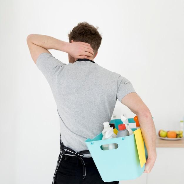 Uomo con cesto di prodotti per la pulizia