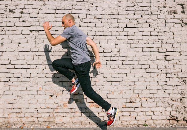 Uomo con corpo in forma saltando e correndo contro il muro di mattoni bianchi