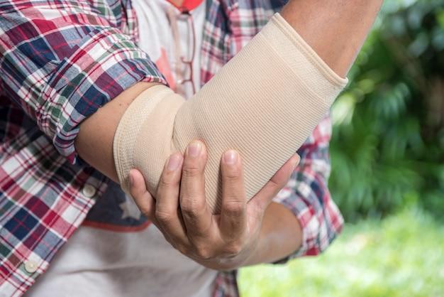 Uomo con dolore al gomito. concetto di sollievo dal dolore