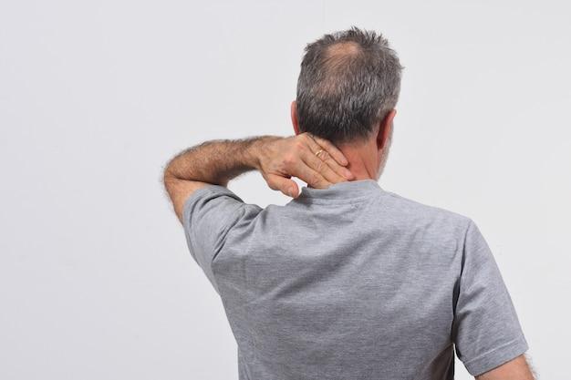 Uomo con dolore sulla nuca su sfondo bianco