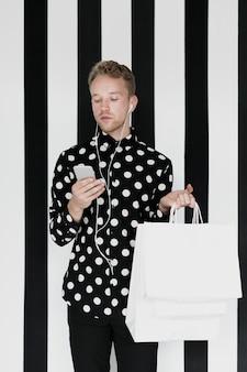 Uomo con eadphones che esamina smartphone