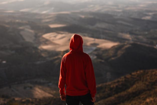 Uomo con felpa rossa con paesaggio sfocato