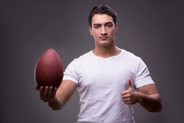 Uomo con football americano nel concetto di sport
