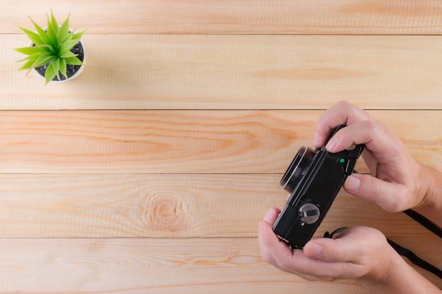Uomo con fotocamera vintage su un tavolo di legno con copia spazio. concetto di giornata mondiale della fotografia.