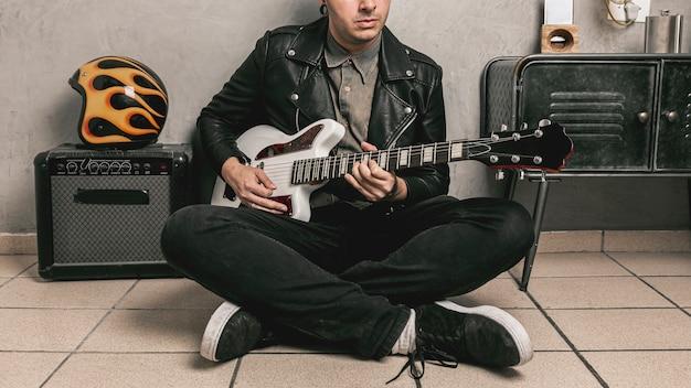 Uomo con giacca di pelle a suonare la chitarra