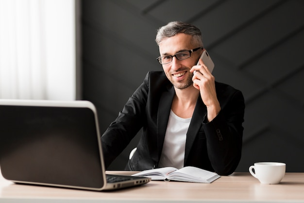 Uomo con giacca nera, parlando al telefono