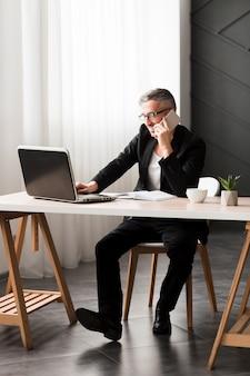 Uomo con giacca nera seduto alla scrivania