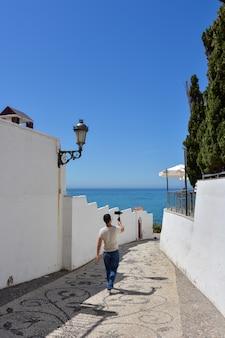 Uomo con gimbal per smartphone che cammina per le strade di una città mediterranea