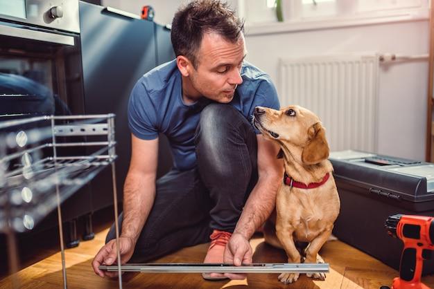 Uomo con gli armadi da cucina della costruzione del cane