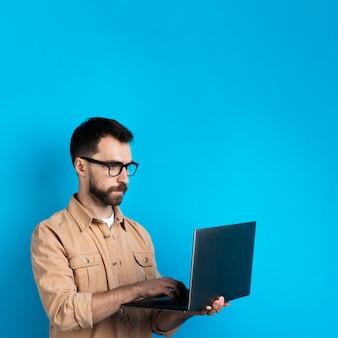 Uomo con gli occhiali che lavora al computer portatile