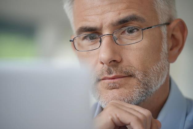Uomo con gli occhiali che lavora su un computer