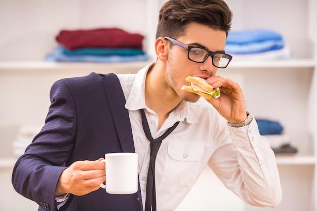 Uomo con gli occhiali che mangia la sua colazione mentre si affretta a lavorare.