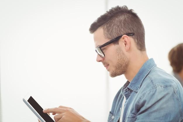 Uomo con gli occhiali che utilizza compressa digitale all'ufficio