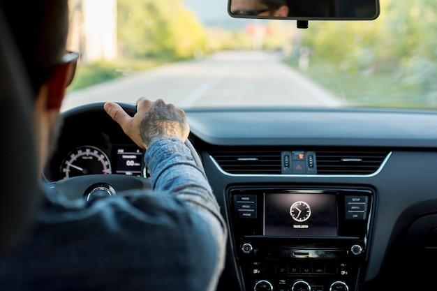 Uomo con gli occhiali da sole alla guida di automobili