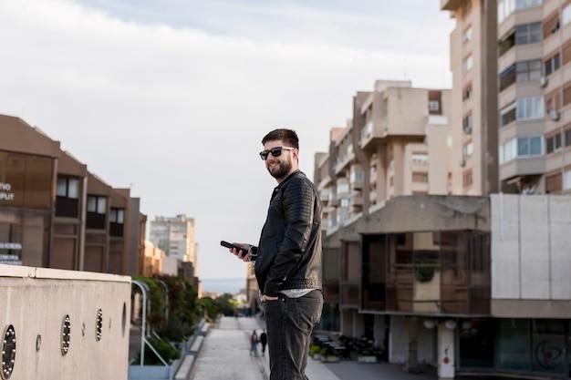 Uomo con gli occhiali da sole che tiene smartphone