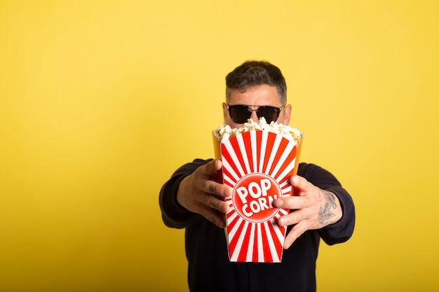 Uomo con gli occhiali da sole defocused che mostrano una scatola piena di popcorn sopra fondo giallo.