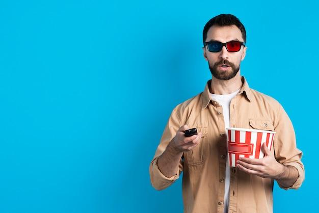 Uomo con gli occhiali di film che indica telecomando