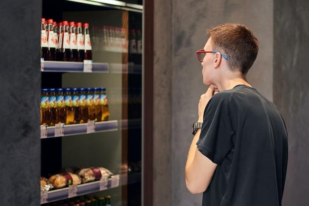Uomo con gli occhiali e guarda scegliendo cosa comprare