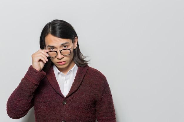 Uomo con gli occhiali in posa e fissando