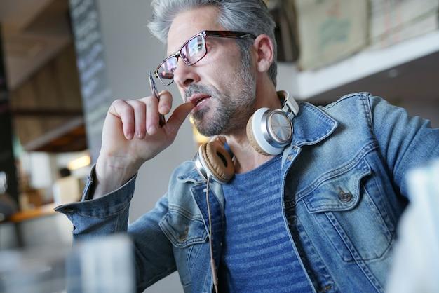Uomo con gli occhiali in un bar