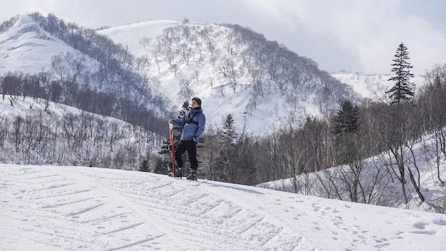 Uomo con gli sci in mano con gli occhiali da sci in montagna invernale neve.