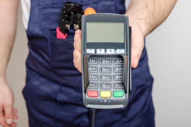 Uomo con gli strumenti che tengono il terminale di pagamento bancario
