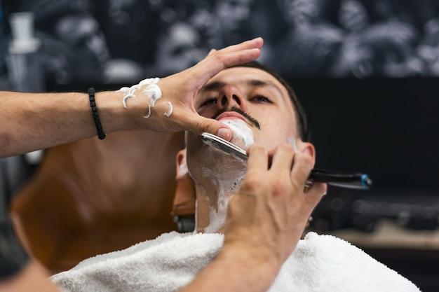 Uomo con i baffi che si fa la barba