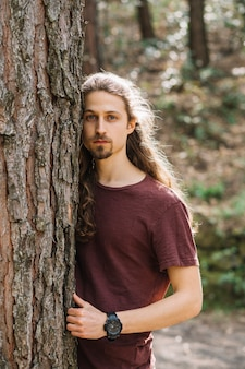 Uomo con i capelli lunghi che abbraccia un albero