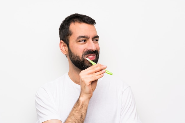 Uomo con i denti di spazzolatura della barba sopra la parete bianca isolata