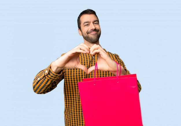Uomo con i sacchetti della spesa che fanno simbolo del cuore a mano su fondo blu isolato