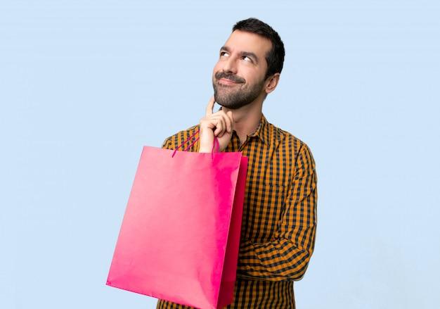 Uomo con i sacchetti della spesa che pensa un'idea mentre guardando su
