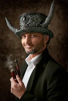 Uomo con il cappello da fumo della tenuta del cappello diabolico
