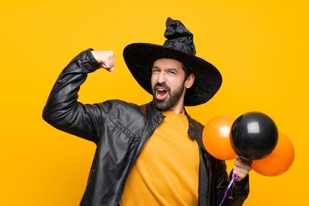 Uomo con il cappello della strega che tiene gli aerostati di aria neri ed arancioni per la festa di halloween che fa forte gesto