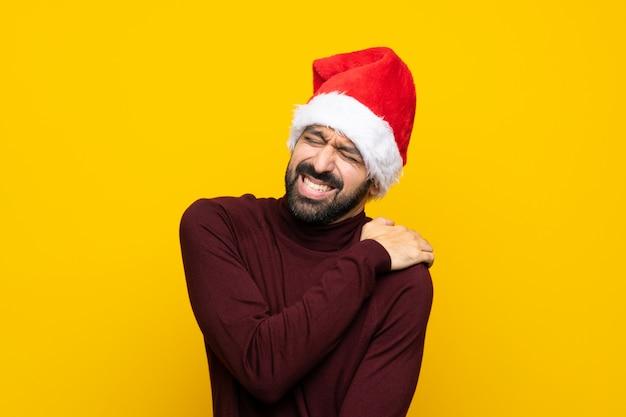 Uomo con il cappello di natale con dolore alla spalla sopra fondo giallo isolato