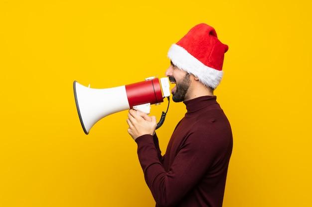 Uomo con il cappello di natale sopra la parete gialla isolata che grida tramite un megafono