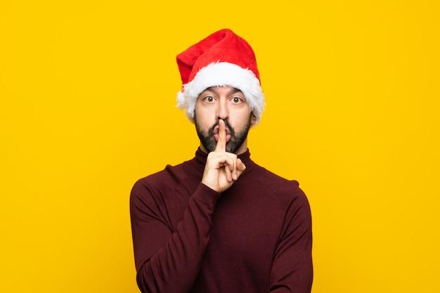 Uomo con il cappello di natale sopra la parete gialla isolata che mostra un segno di gesto di silenzio che mette il dito in bocca