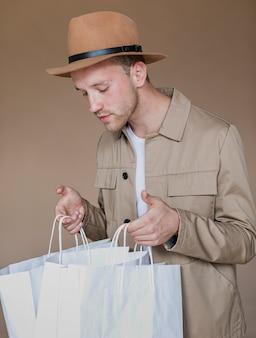 Uomo con il cappello marrone che guarda in sacchetti della spesa