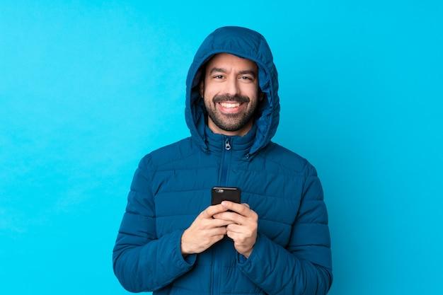 Uomo con il cappotto di inverno sopra la parete isolata