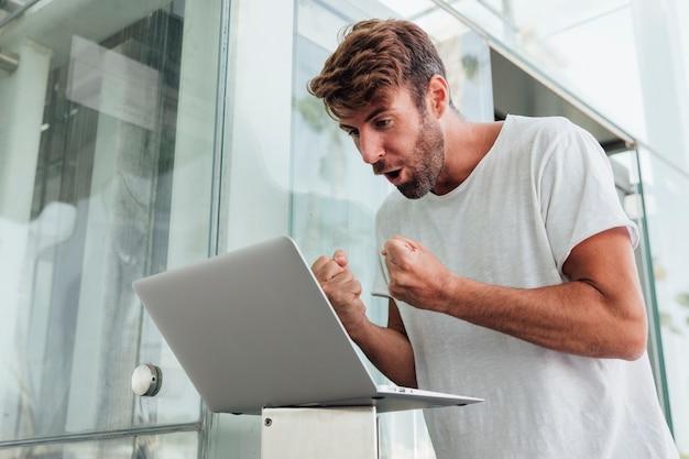 Uomo con il computer portatile che celebra con i pugni