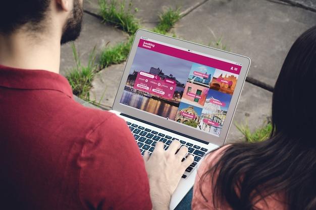 Uomo con il computer portatile che prenota un hotel sul sito web