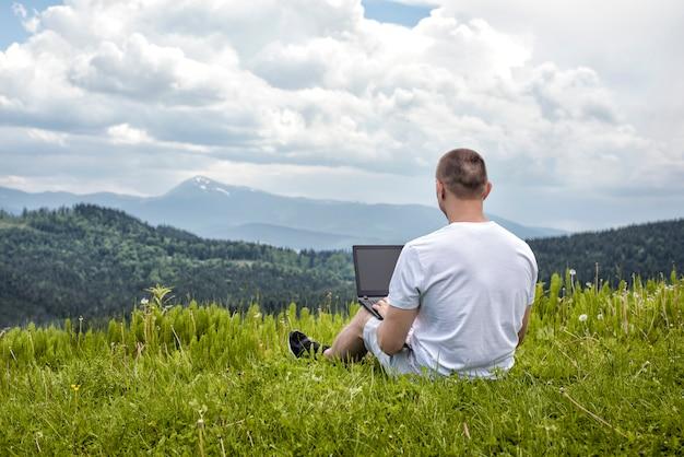 Uomo con il computer portatile che si siede sull'erba verde