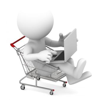 Uomo con il computer portatile dentro il carrello. concetto di shopping online.