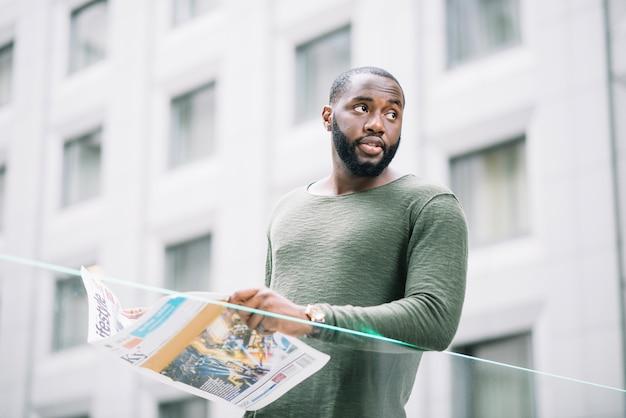 Uomo con il giornale che osserva via