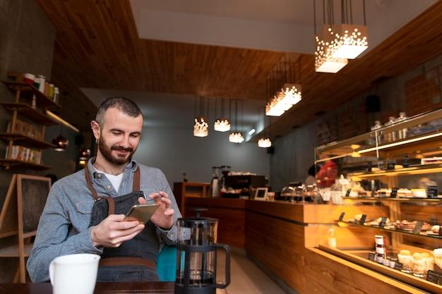 Uomo con il grembiule sul telefono in caffetteria