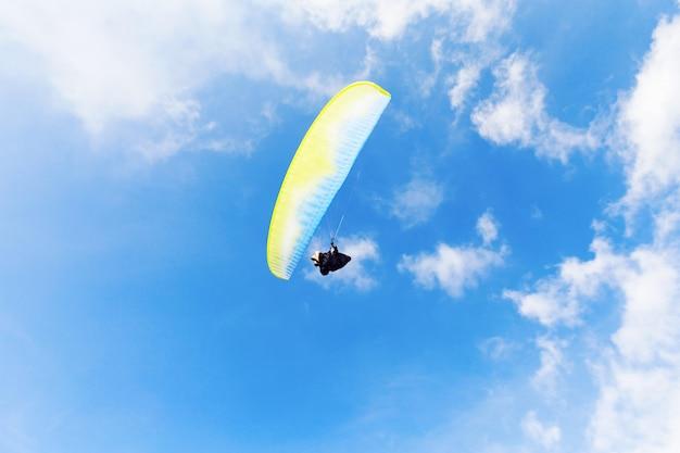 Uomo con il paracadute giallo sopra il cielo blu