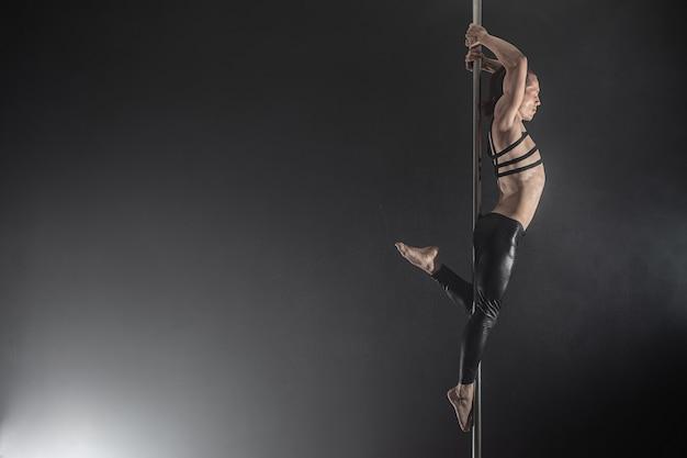 Uomo con il pilone ballerino del palo maschile danza su uno sfondo nero