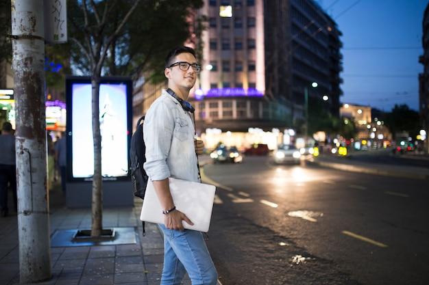 Uomo con il portatile in piedi sul marciapiede di notte