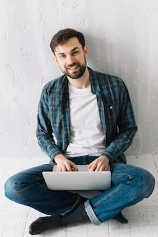 Uomo con il portatile seduto vicino a muro