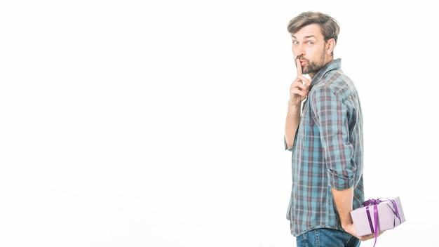 Uomo con il regalo del biglietto di s. valentino che fa gesto di silenzio su fondo bianco