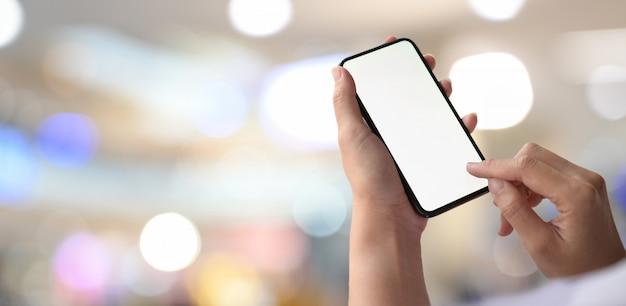 Uomo con il telefono cellulare che mostra schermo in bianco sopra la priorità bassa del bokeh